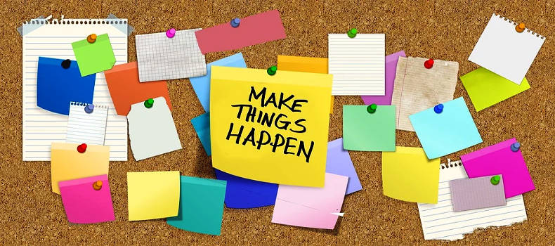 Make Things Happen Post-It on corkboard with other blank Post-Its.
