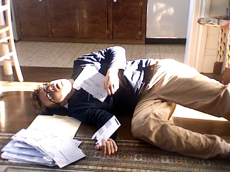 Man laying on floor with papers for managing your business expenses post.