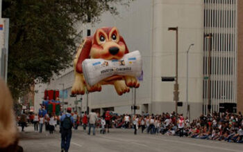 Inflatable dog float holding newspaper for sell your book to locals post.