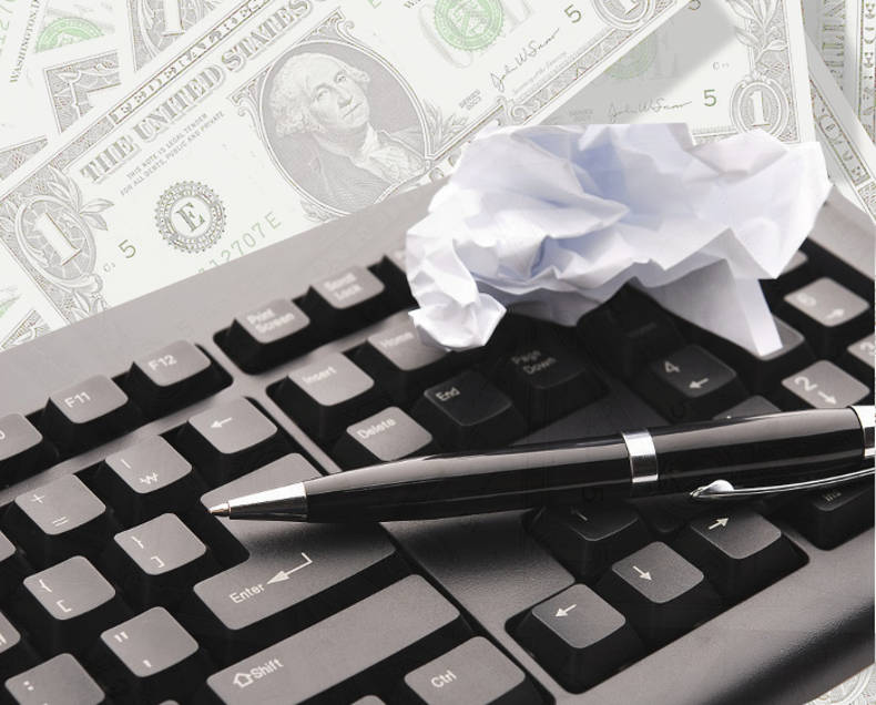 Writing from home - money background, computer keyboard, wadded paper and pen.